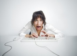 scared-woman-hitting-keyboard-at-her-desk-computer-300x218